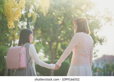 Asian Mother holding hand of daughter with backpack going to school,Back to school concept