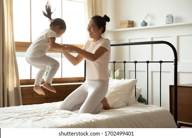 Asian mother holding hands of little toddler daughter while she jumping on bed. Family spend together active energetic funny time in the morning in bedroom. Happy motherhood, cozy modern home concept