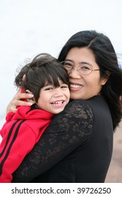 Asian mother holding her little toddler boy outdoors by beach