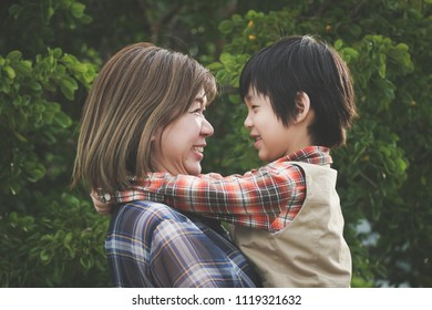 Asian mother holding her son in the park