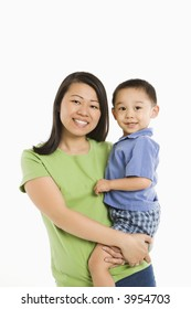 Asian mother holding son on hip smiling in front of white background.