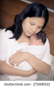 Asian mother holds close her mixed race 10 day old newborn baby boy in her bedroom