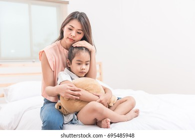 Asian mother hugging and comforting her sad daughter in bed room