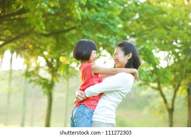 Asian mother hugging her daughter at outdoor park