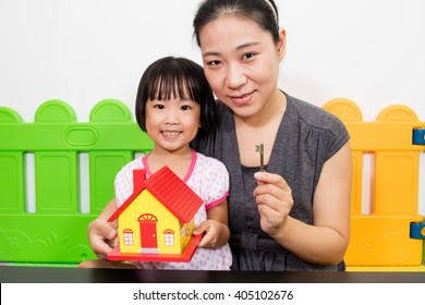 Asian Mother and Little Chinese Girl Holding Key for Property Concept at Playground