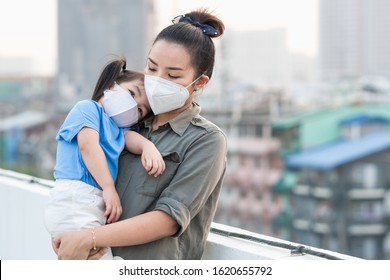 Asian mother and little young daughter wearing mask for prevent dusk pm 2.5 bad air pollution on deck in Bangkok city Thailand 2020.