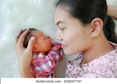 Asian mother lying with her son on white fur background. Close-up of baby and mom.