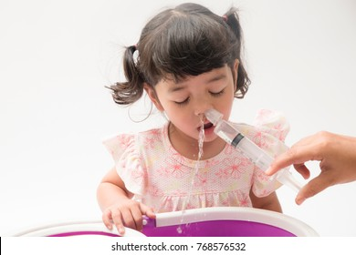 Asian mother making nasal wash for her baby girl by flushing kid'nose with syringe and saline. An Irrigation can benefit people who have sinus problems,nasal allergies isolated on white background