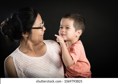 Asian mother and mixed race 2 year old boy playing together on a black background