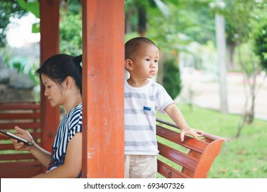 Asian mother paying attention to smart phone instead of playing with 1 year and sixth months son