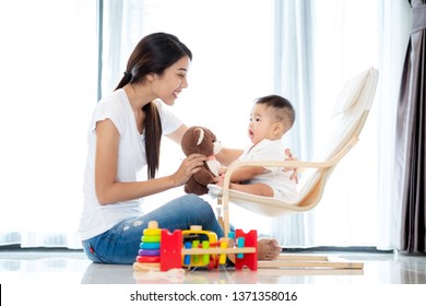 Asian mother play with her baby on arm chair by teddy bear and wooded toy