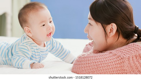 asian mother play with her baby on the bed