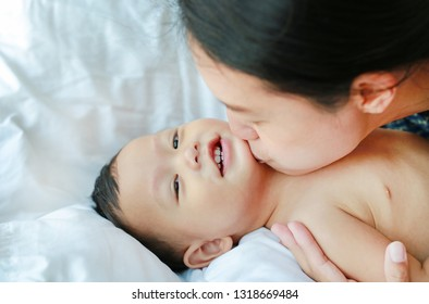 Asian Mother is playing and kissing her little baby boy on the bed.