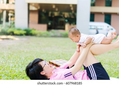 Asian  mother playing and taking care of  baby at park