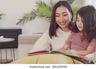 Asian mother read book to her mixed daughter girl at home, spending family quality time together, homeschooling education concept
