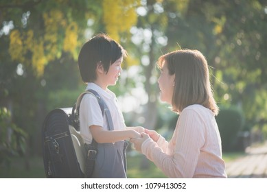 Asian mother  saying goodbye to her son as he leave for School,back to school concept