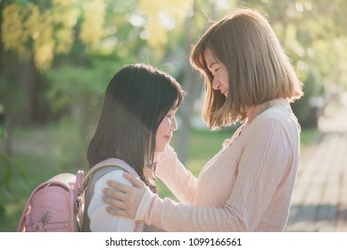 Asian mother saying goodbye to her daughter as she leave for School,back to school concept