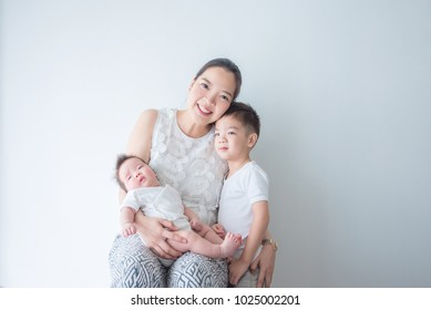 Asian mother smiles while holding her little child and hug her son