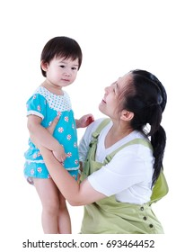 Asian mother smiling and playing with her daughter. Happy family spending time together. Isolated on white background. Parenthood lifestyle concept. Mother's Day celebration. Studio shot.