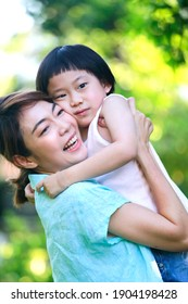 Asian mother is smiling while holding her son up over a green garden background. Quality family time concept.