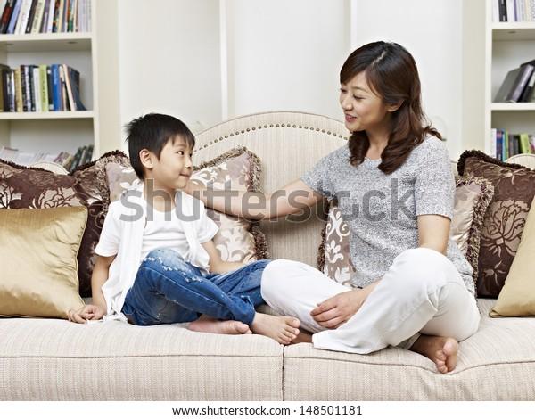 家のソファで会話をするアジア人の母子