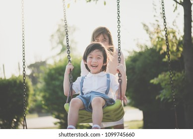 Asian mother and son having fun on swing together in the park