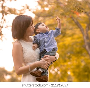 Asian mother and son having fun outdoors in autumn