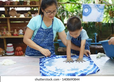 Asian mother and son playing art together by making northern thai blue dye fabric cloth textiles with hand prints