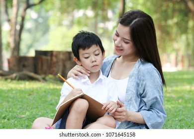 Asian Mother and son playing and learning and writing a book and picnic in park in a holiday