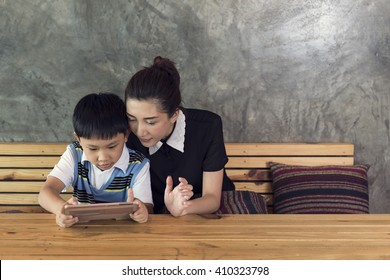 asian mother and son playing tablet together