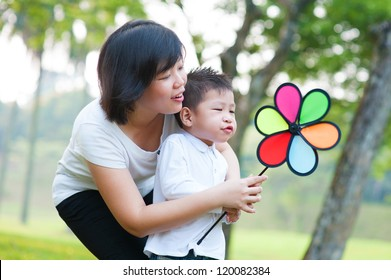 Asian mother and son playing windmill at outdoor park