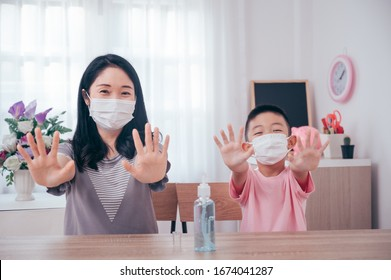 Asian mother and son using wash hand sanitizer gel pump dispenser, Washing hand with Alcohol Sanitizer, protect the virus and bacterias.
