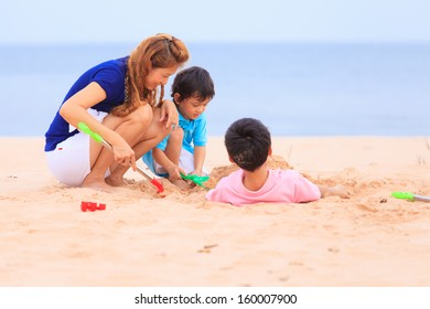 Asian mother and sons playing on sand beach