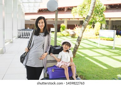 Asian mother stood carrying a bag next to her daughter sitting on a suitcase on a trolley at the airport