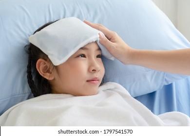Die asiatische Mutter kümmert sich um ihre kranke Tochter, die Fieber hatte und in der Kinderklinik. Gesundheitswesen und medizinisches Konzept