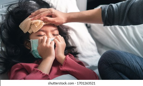 Asian mother take cool towel for reduce high fever on sick girl forehead, girl wearing medical protective face mask and coughing, Selective focus, Healthy and infection concept