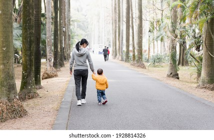 An Asian mother takes her son for a walk in the park