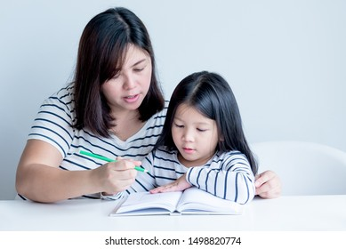 An Asian mother is teaching a 6 year old daughter to learn to write and read On white table and white wall background, concept to family and education.