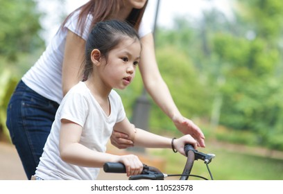 Asian Mother teaching daughter cycling at the park in the evening