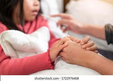 Asian mother touch hand young daughter for encouragement, mother measuring temperature girl with digital thermometer, Sick child have  high fever, Selective focus, Healthy and infection concept