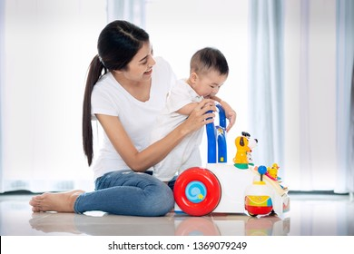 Asian mother traning walking to her baby by walking toy