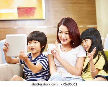 asian mother and two children son and daughter taking a selfie using digital tablet.