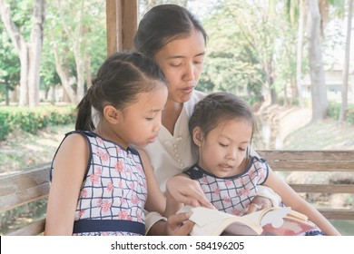 Asian mother and two daughters sitting in the park reading a book.