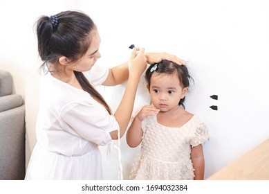 Asian mother use tape for measure her daughter's height. Mom and kids, education, family relationship, child care, children growth evolution concept.
