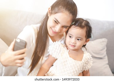 Asian mother are using cell phones take coffee with her daughter.The love of a mother with a daughter.