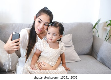 Asian mother are using cell phones take selfie photo with her daughter. The love of a mother with a daughter.