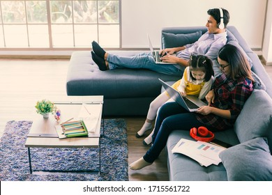 Asian mother using laptop computer to work on sofa in living room while teach and explain her half little cute daughter. Caucasian father sitting and working with notebook in background, happy family.