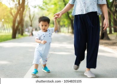 Asian mother walks with her child holding his hand in the spring park. Responsible parenting concept