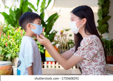 Asian mother wear a face mask to her son before go to market, this image can use for family, covid19 and health concept