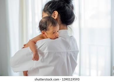 Asian mother with white shirt place upon the shoulder of little newborn baby after give milk and the baby look sleepy.
